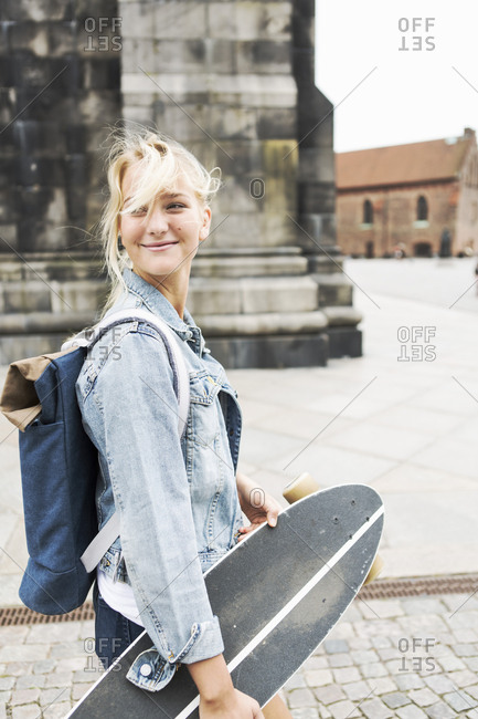 Smiling teenage girl holding skateboard while walking on cobbled street in city