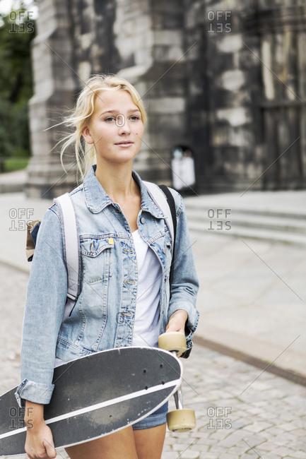Teenage girl holding skateboard walking on cobbled street in city