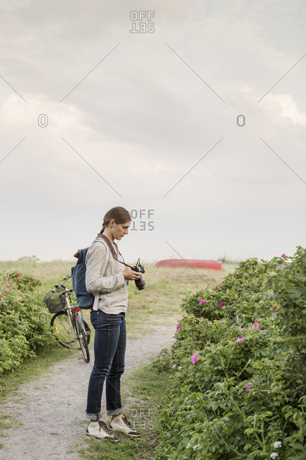 Woman photographing plants while standing on dirt road against sky