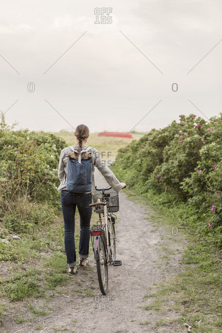 Rear view of woman carrying backpack walking with bicycle on footpath amidst plants