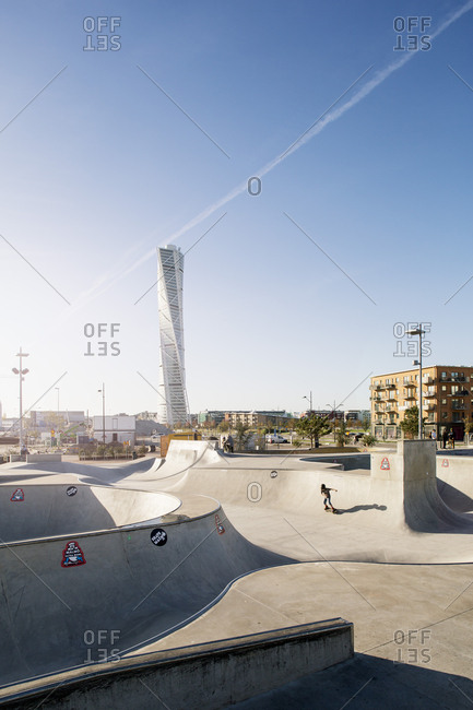 Malmo, Sweden - December 21, 2016: Man playing at skateboard park against Turning Torso in city on sunny day