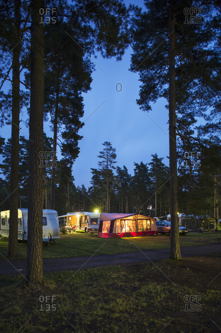 Illuminated caravans parked in travel trailer park amidst trees at dusk