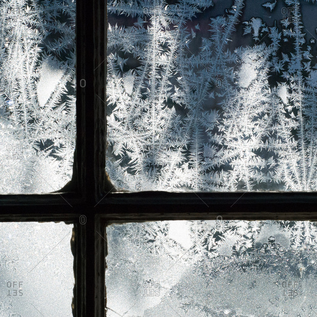 Frost and sunshine dancing on an old window pane
