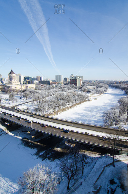 Overhead view of snowy river and cityscape under bright blue winter sky