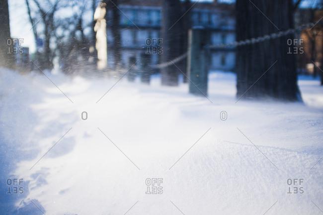 Snow drifts across city sidewalks after a blizzard