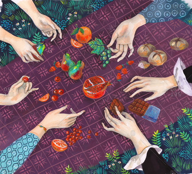 Hands picking fruits, bread and chocolates from a picnic blanket,