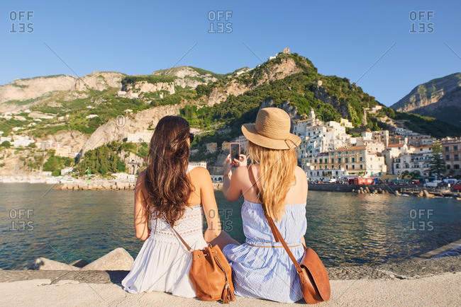 Beautiful girl friends take photographs of Italy coast using smart phone