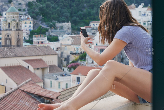 Beautiful girl friends take photographs of Italy coast