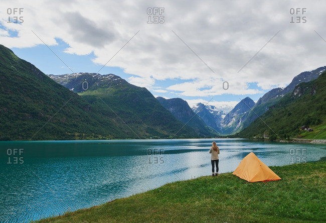 Woman camping at beautiful lake in yellow tent