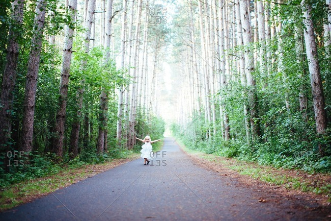 Little girl running on a paved path in the woods