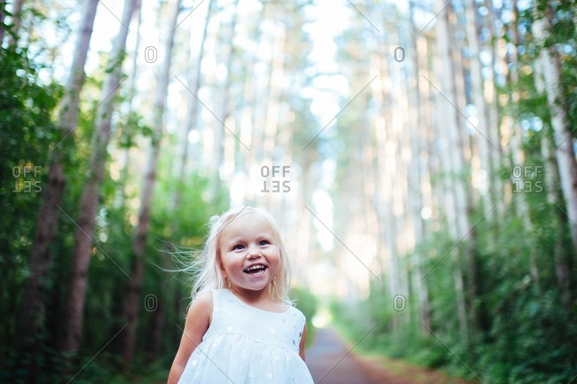 Little girl standing in the woods smiling