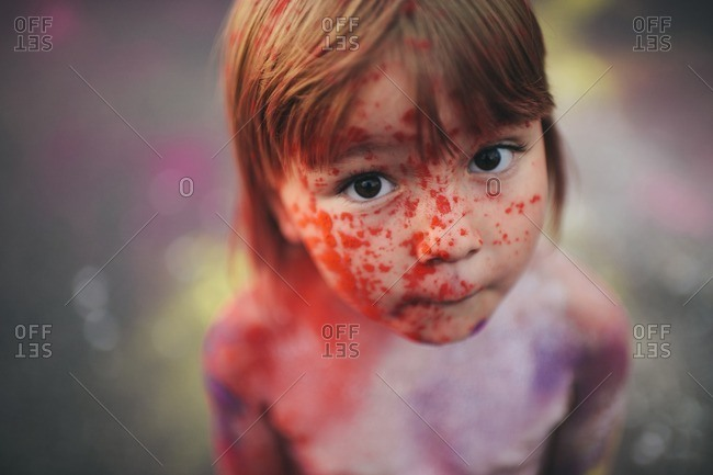 Face of a girl splattered with different colors of paint