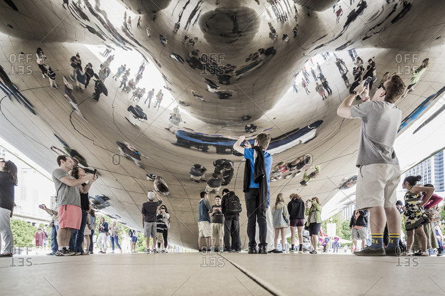 Chicago, Illinois - 6/19/15: Downtown Loop, taking photos under the Cloud Gate sculpture (popularly knows ad The Bean)