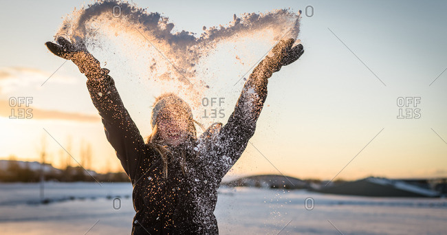 Young woman throwing snow in the air in the shape of a heart