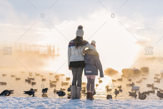 Two girls standing together watching ducks in lake in winter