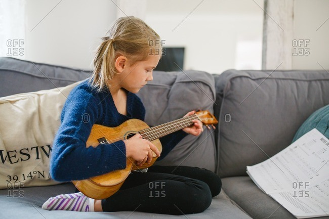 Little girl practicing ukulele