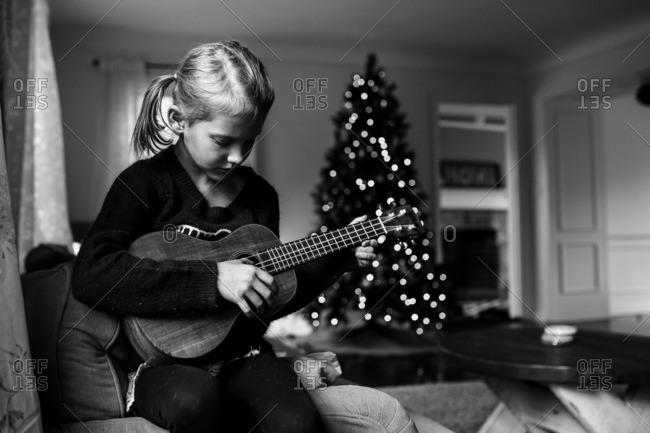 Girl playing ukulele at Christmastime
