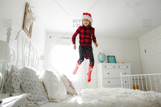 Girl jumping on bed in Santa hat