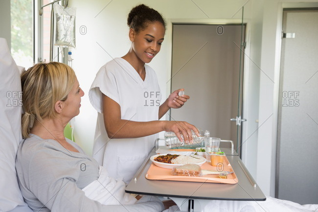 Female nurse serving food to patient on hospital bed