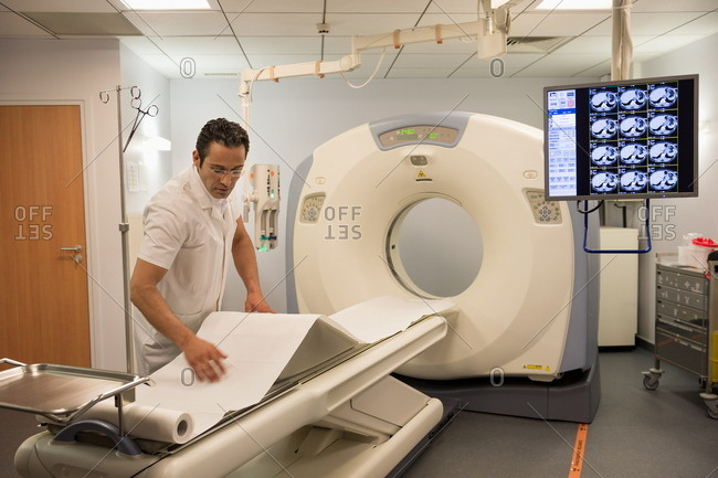 Male doctor preparing medical MRI scanner in hospital