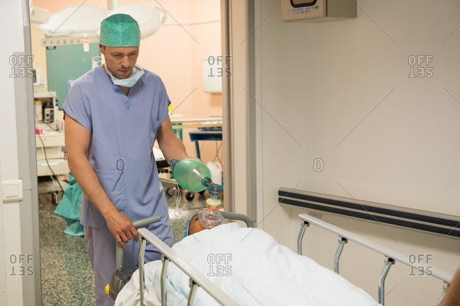 Surgeon moving patient into operating room