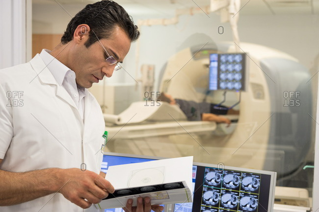 Male doctor examining MRI scan report in medical scan room