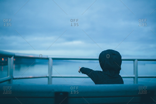 Boy standing at a waterfront railing pointing