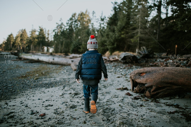 Boy in a knit hat walking on a beach with driftwood logs