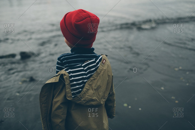Boy in a coat and knit hat standing on a beach