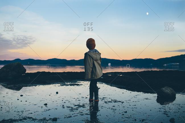 Boy standing on a beach at sunset