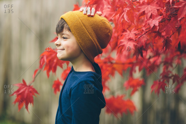 Boy in a knit hat standing in front of an autumn tree