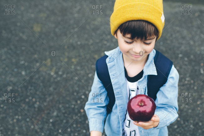 Boy standing on pavement holding an apple