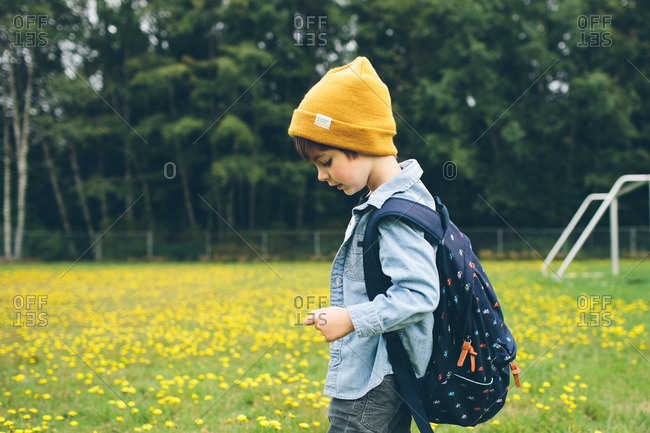 Boy with a backpack standing in a field of yellow flowers