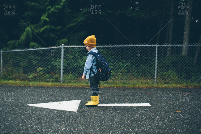 Boy with a backpack standing on an arrow painted on pavement