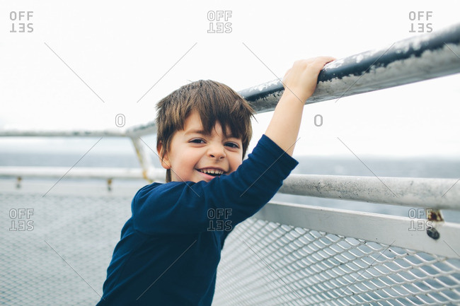 Boy standing at a railing smiling