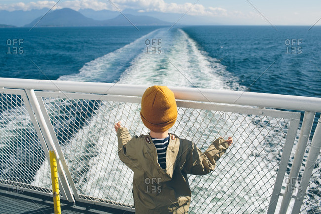 Boy standing at the back of a ferry boat looking at the sea