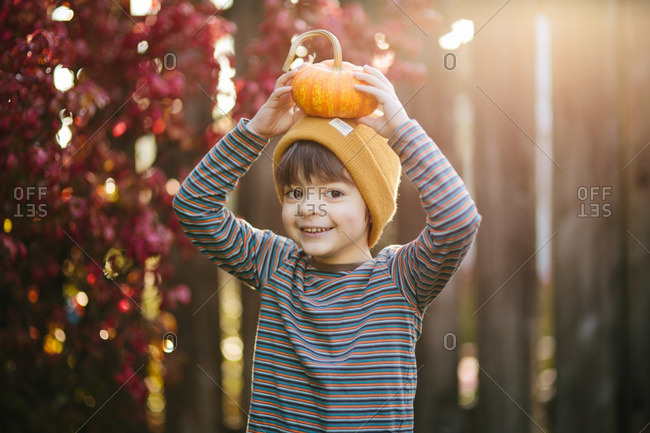 Boy in a yellow knit hat standing with a pumpkin on his head