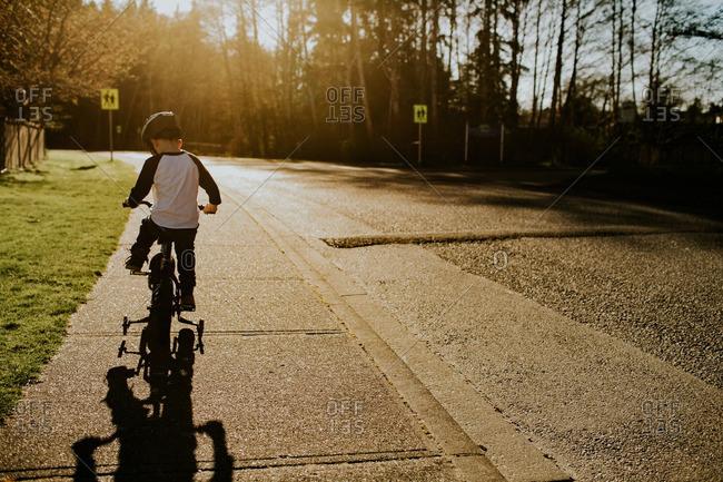Boy riding a training bike on a sidewalk