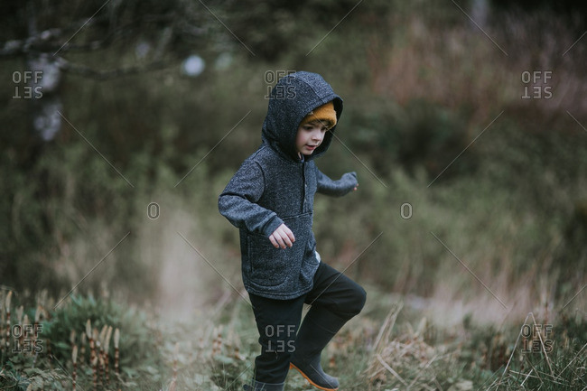 Boy wearing a hooded jacket in a field