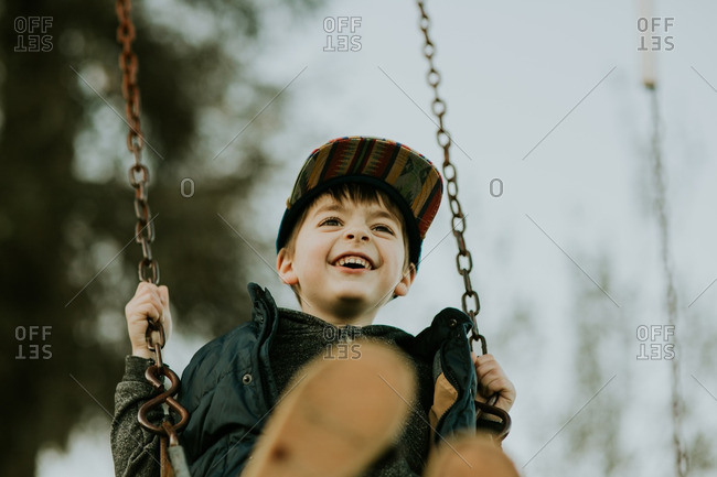 Little boy in a multi-colored hat on a swing set