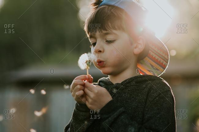 Boy in a backwards cap blowing dandelion seeds