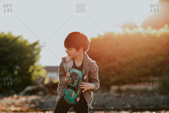 Boy playing with a toy car outside