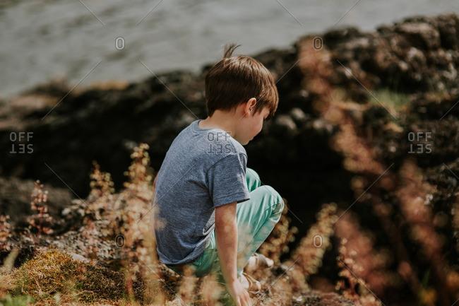 Boy crouching on a rock at a beach