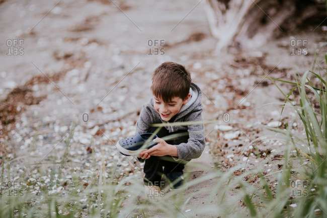 Little boy playing with his shoe on a beach
