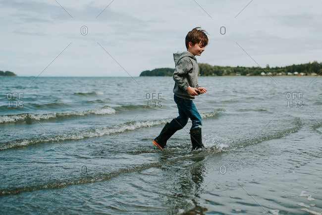 Boy playing in shallow surf at a beach