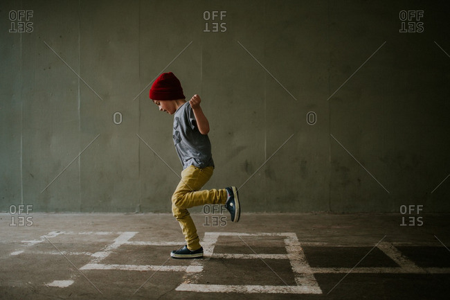 Boy in a red knit hat playing hopscotch