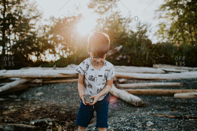 Boy collecting rocks on a stone beach with driftwood