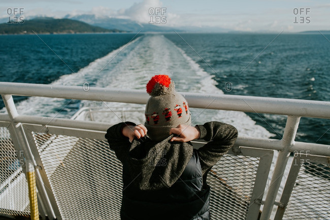 Boy in a knit hat standing at the back of a ferry boat