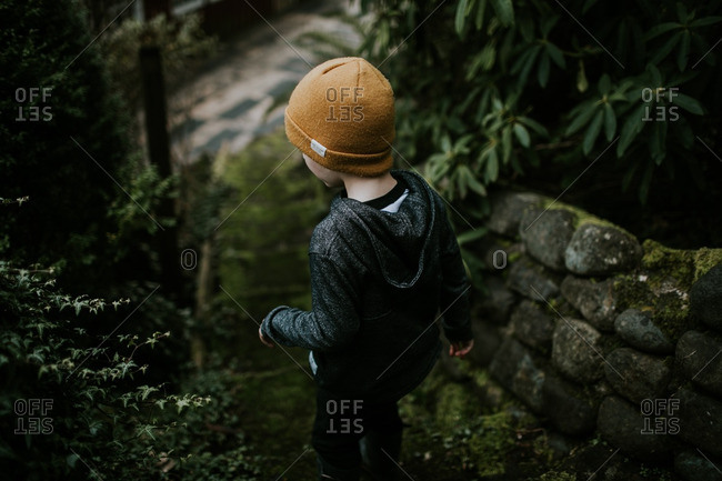 Little boy walking on mossy steps in a garden