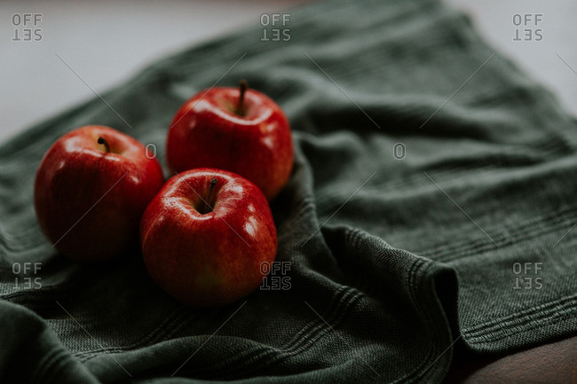Three red apples on a green kitchen cloth